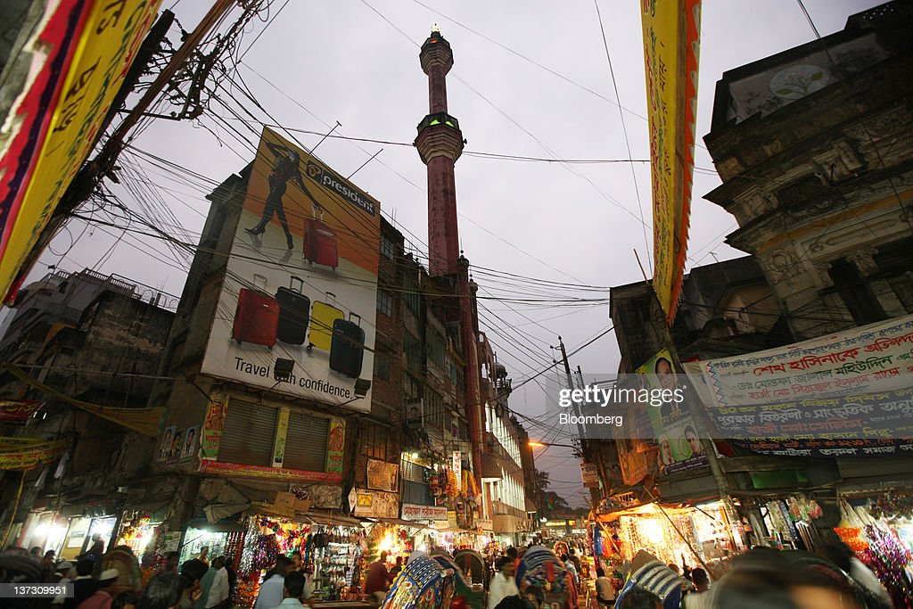 A mosque stands behind shops in the Old Market in Dhaka, Bangladesh, on Saturday, Jan. 7, 2012. Bangladesh's central bank this month raised interest rates for the second time in four months to curb inflation that has exceeded 9 percent since the start of 2011. Photographer: Tomohiro Ohsumi/Bloomberg via Getty Images