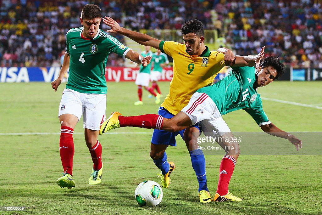 Mosquito (C) of Brazil is challenged by Pedro Teran (L) and Erick Aguirre of Mexico during the FIFA U-17 World Cup UAE 2013 Quarter Final match between Brazil and Mexico at Al Rashid Stadium on November 1, 2013 in Dubai, United Arab Emirates.