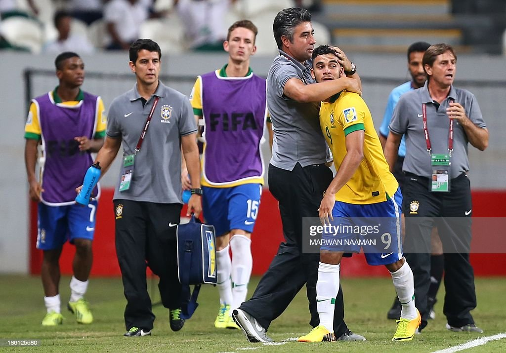 Mosquito (R) of Brazil jubilates with his coach Alexander Gallo after scoring a goal against Russia during their game in round 16 of the FIFA U-17 World Cup at the Mohammad Bin Zayed Stadium in Abu Dhabi, on October 28, 2013. Brazil qualified to the quarter final beating Russia 3-1. AFP PHOTO/MARWAN NAAMANI