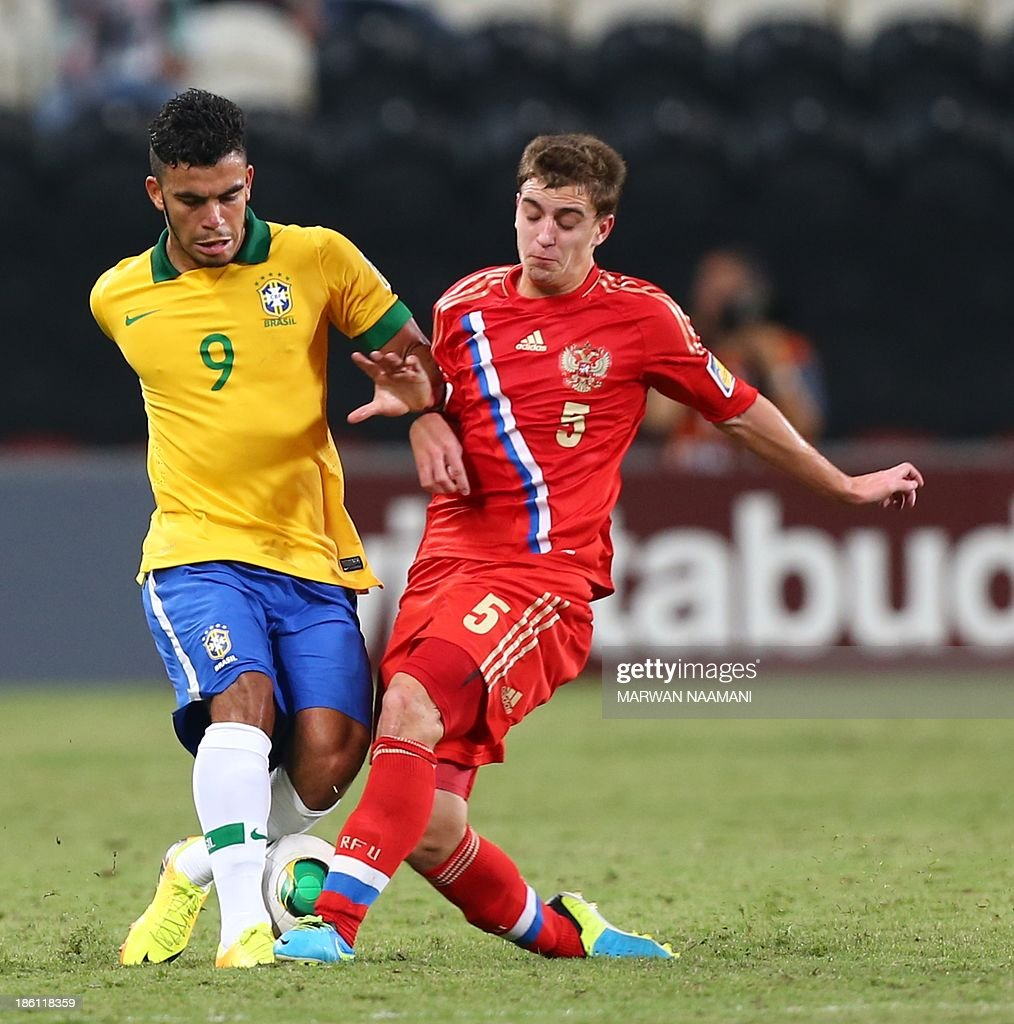 Mosquito (L) of Brazil vies for the ball against Denis Yakuba of Russia during their game in round 16 of the FIFA U-17 World Cup at the Mohammad Bin Zayed Stadium in Abu Dhabi, on October 28, 2013.