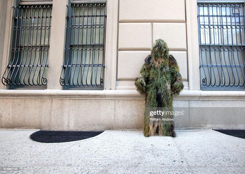 Moss man hiding on street