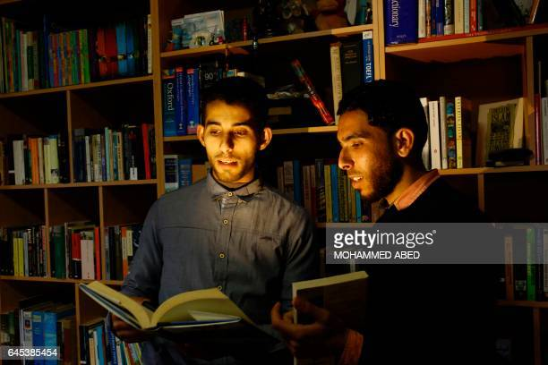 Mossab Abo Toha and his friend Shafi Salem who is helping Abu Toha set up the 'Library and Bookshop for Gaza' project pose for a photo holding books...