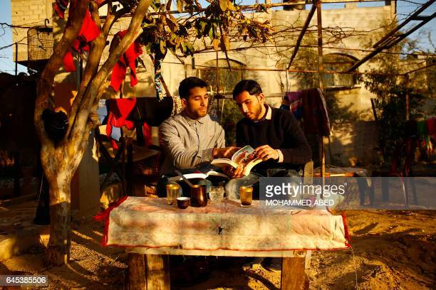 TOPSHOT Mossab Abo Toha and his friend Shafi Salem who is helping Abu Toha set up the 'Library and Bookshop for Gaza' project pose for a photo in the...