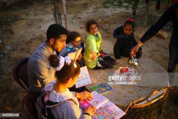 TOPSHOT Mossab Abo Toha who is collecting english books for his 'Library and Bookshop for Gaza' project reads english books with children in the...