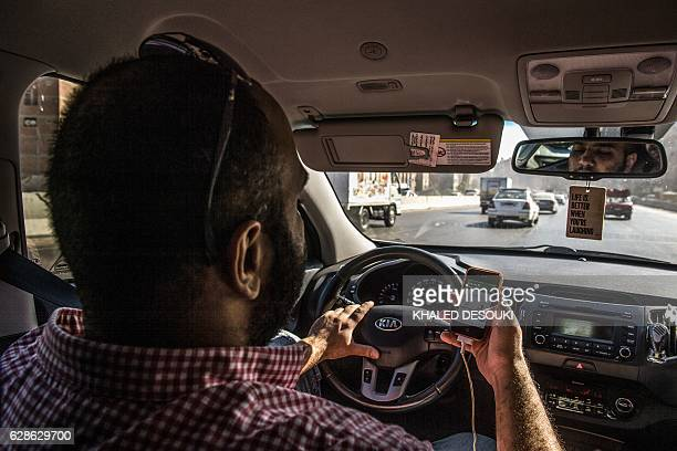 Mostafa Ekram a corporate sales manager uses a navigation application on his mobile phone as he drives to work in the Egyptian capital Cairo on...