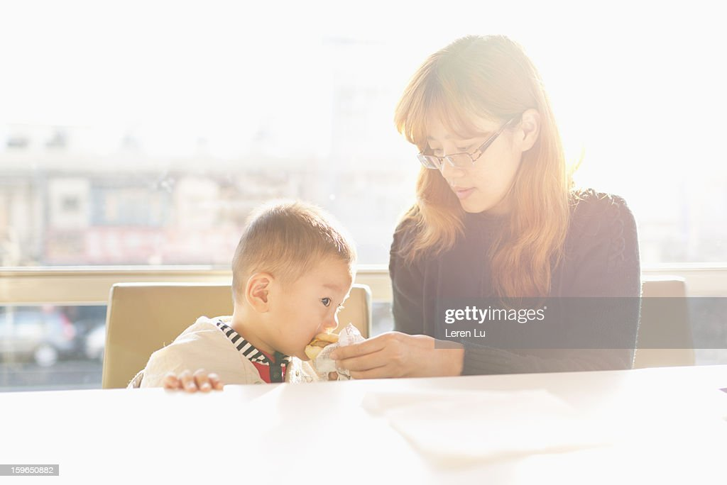 Motehr and child in fast food restaurant : Stock Photo