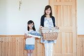 Motehr and daughter holding cloths and basket