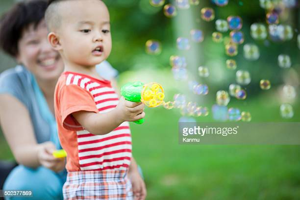 Mother accompanied child blowing bubbles outdoors