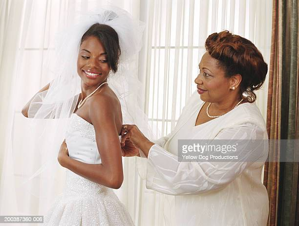 Mother adjusting bride's dress, side view