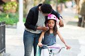 Mother adjusting daughter's bicycle helmet