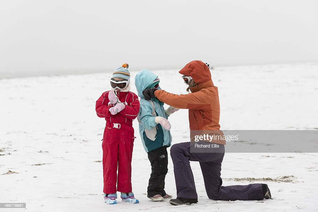 A mother adjusts her childrens clothing on the beach after a rare ice storm blanked the normally warm historic city on January 29, 2014 in Charleston, South Carolina. The storm closed bridges and roads as a winter weather blanketed the region.