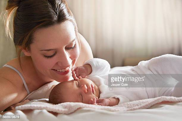 Mother admiring newborn baby on bed
