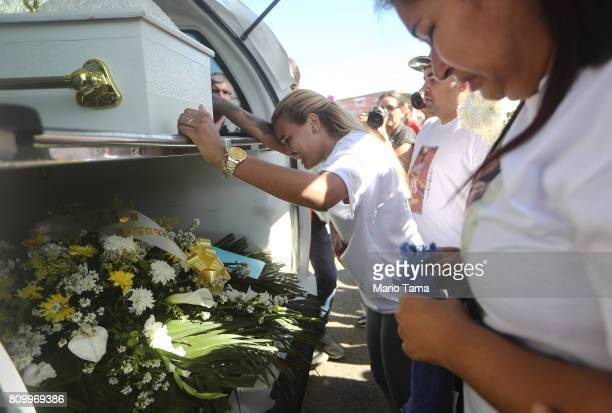 Mother Adriana Maria dos Santos and friend Laisa walk with the casket toward the gravesite during the funeral of Vanessa dos Santos who was shot in...
