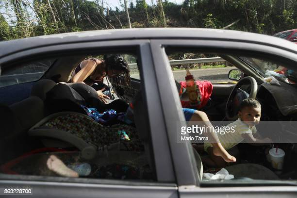 Mother Anais Rivera puts items into her car with her three children after bathing and washing clothes with water from a mountain stream nearly one...