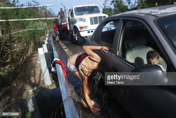 Mother Anais Rivera rinses her hands and feet with water funneled from a mountain stream before entering her car with her three children nearly one...