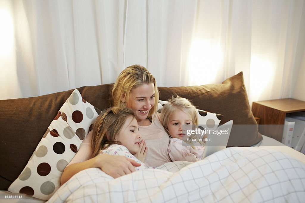 Mother and 2 kids reading bedtime story on tablet : Stock Photo