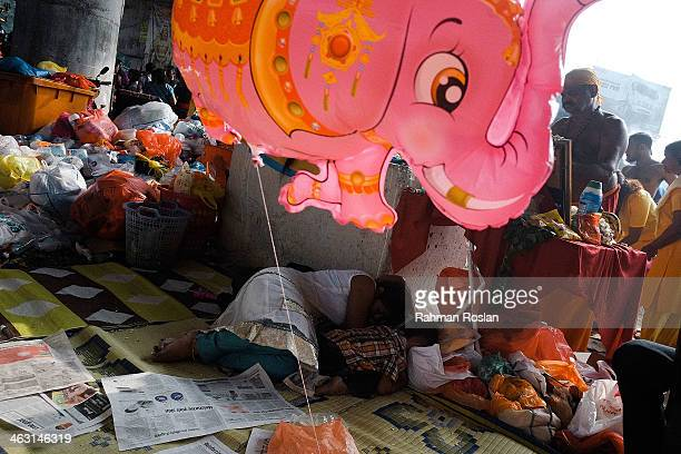 A mother and a child sleep behind an altar during the Thaipusam festival on January 17 2014 in Kuala Lumpur Thaipusam is a Hindu festival celebrated...