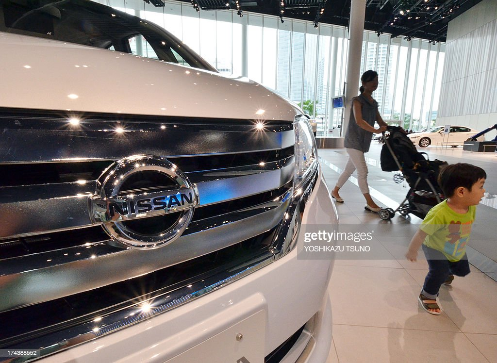 A mother and a child walk past Japanese auto giant Nissan Motor's mini vehicles at the company's showroom in Yokohama, suburban Tokyo on July 25, 2013. Nissan on July 25 said its April-June net profit jumped 14 percent to $821 million, as it pointed to improved market share in Japan and North America. AFP PHOTO / Yoshikazu TSUNO