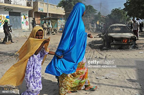 A mother and a child walk past the wreckage of a car bomb in the Wardhigley District south of Mogadishu on February 27 2015 The bomb killed one...