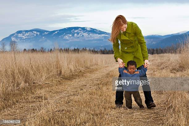 mother and adopted son walking together outdoors in winter