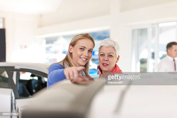 Mother and adult daughter looking at a new car