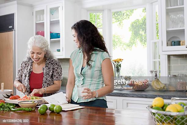 Mother and adult daughter preparing food in kitchen