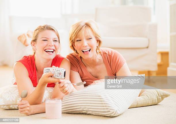 Mother and adult daughter relaxing at home, watching tv
