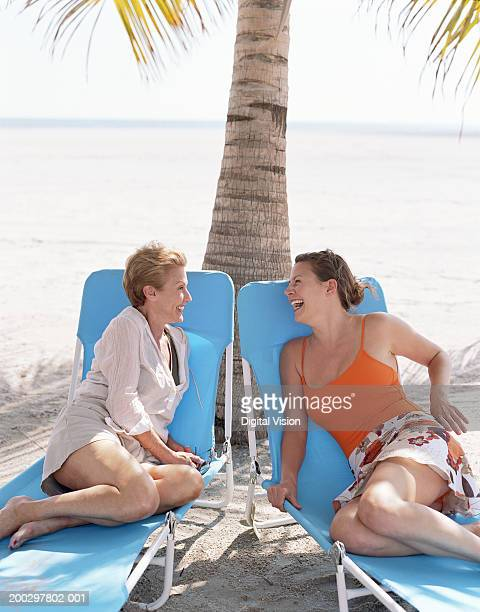 Mother and adult daughter relaxing on sun loungers on beach, laughing