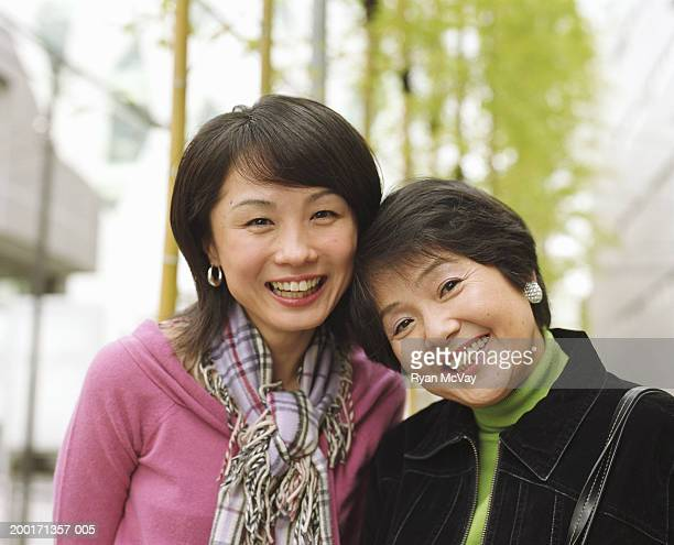 Mother and adult daughter smiling, portrait
