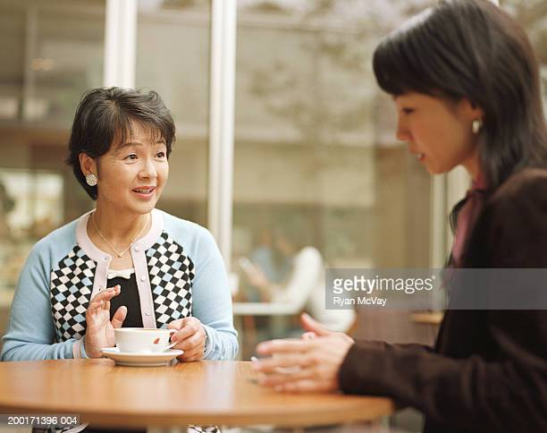 Mother and adult daughter talking in cafe (focus on mother)