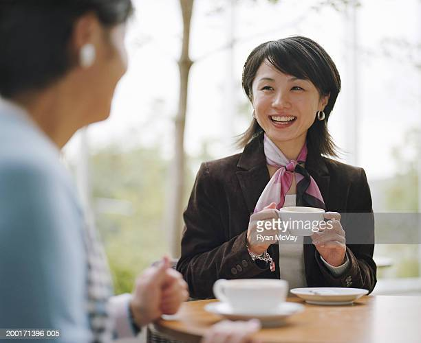Mother and adult daughter talking in cafe (focus on young woman)