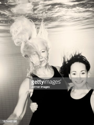 Mother and adult daughter underwater : Stock Photo