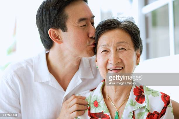 Mother and adult son together, son giving mother a kiss