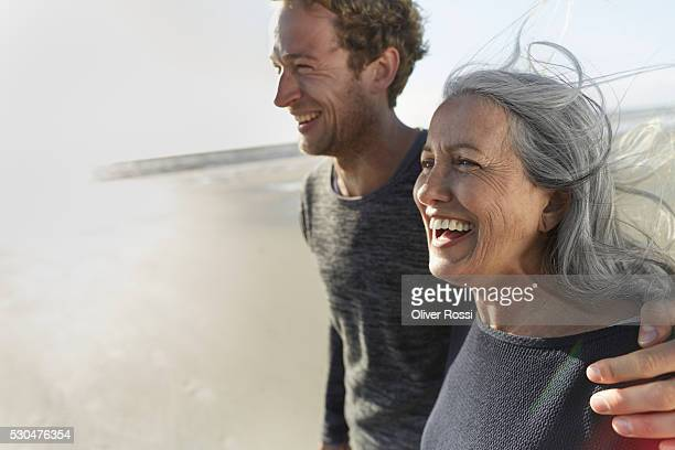 Mother and adult son walking on beach