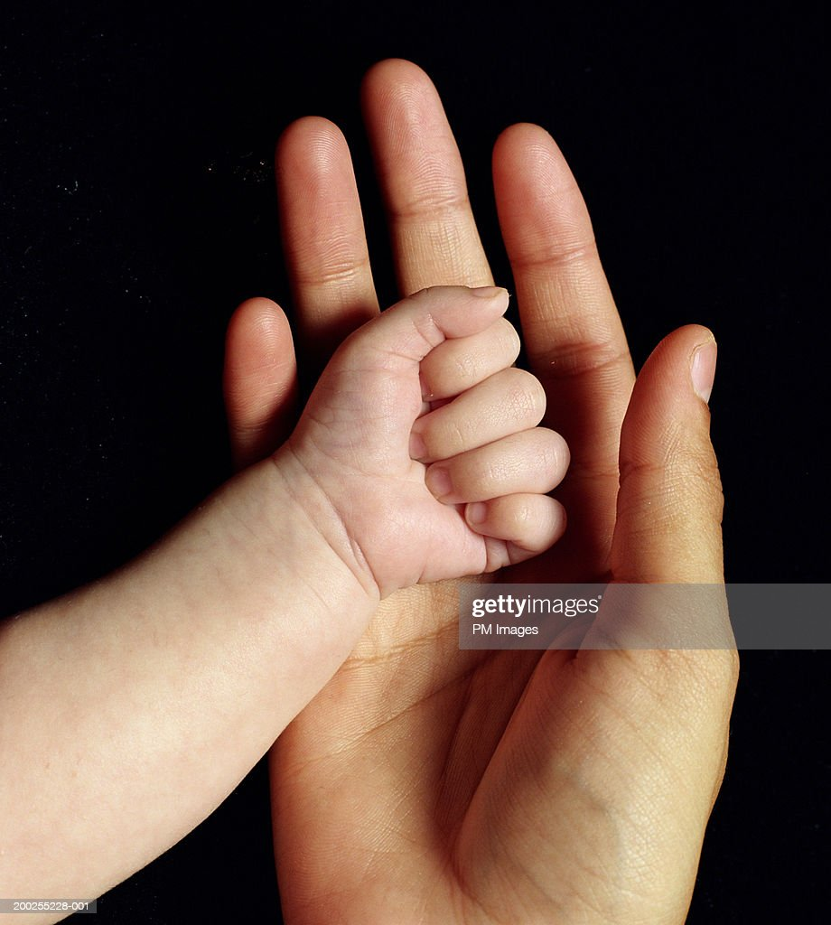 Mother and Baby boy (0-3 months) hands, close-up : Stock Photo