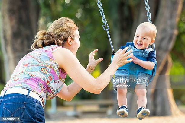 Mother and baby boy having fun in a park