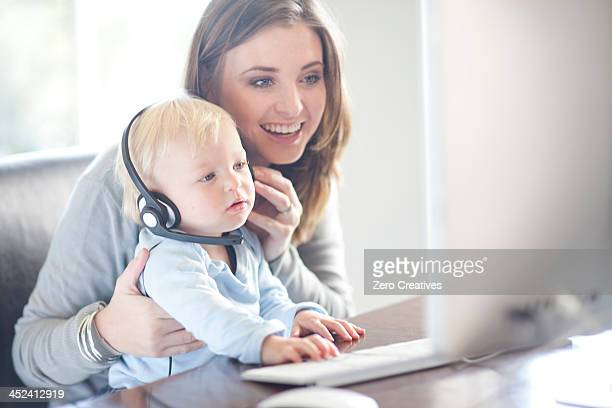 Mother and baby boy looking at computer screen
