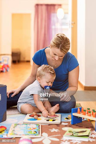 Mother and baby boy playing toys on floor at home