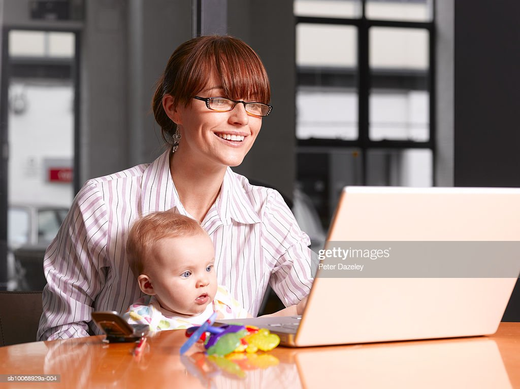 Mother and baby boy (6-11 months) working on laptop : Foto de stock