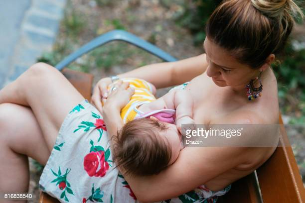 Mother and baby breastfeeding in park
