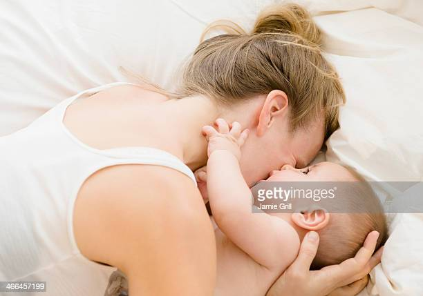 Mother and baby cuddling in bed