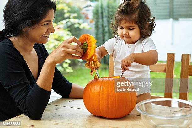 Mother and Baby Daughter Carving a Pumpkin