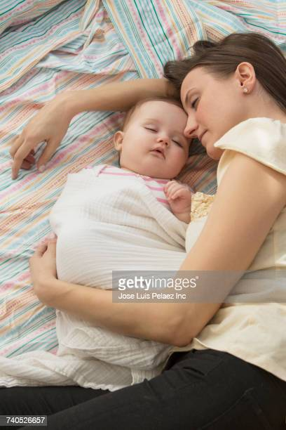 Mother and baby daughter napping on bed