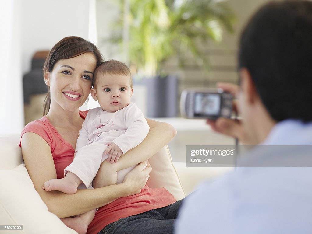 Mother and baby daughter posing while father takes a picture : Stock Photo