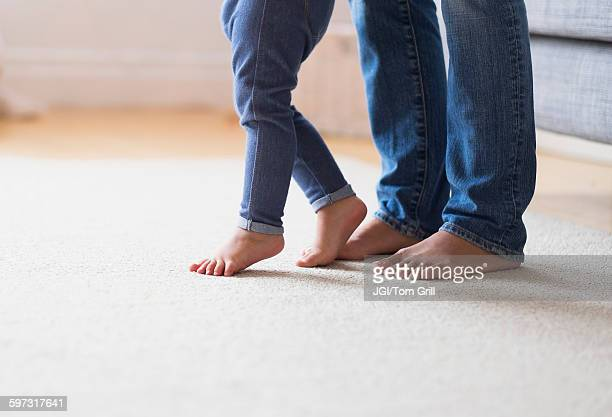Mother and baby daughter with bare feet