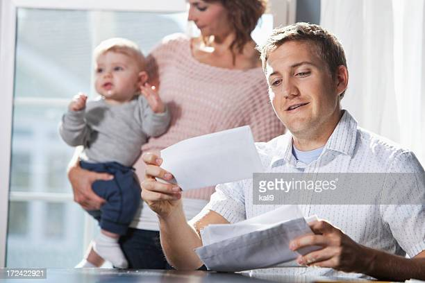 Mother and baby, father paying bills