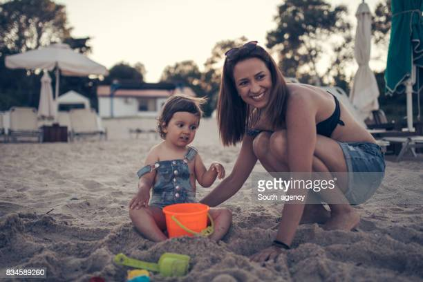 Mother and baby girl having fun in sand
