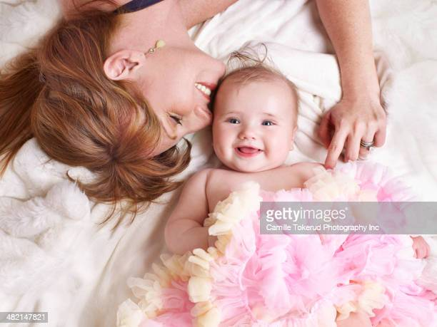 Mother and baby girl laying on bed
