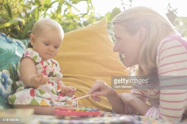 Mutter und baby Mädchen spielen mit Xylophon im Freien
