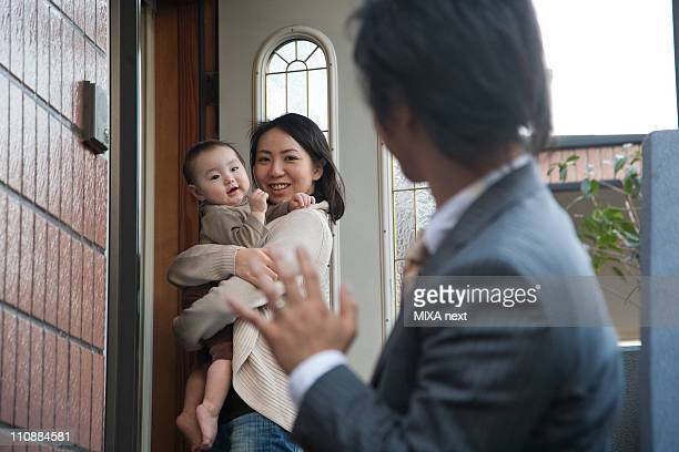 Mother and Baby Girl Smiling to Father at Door